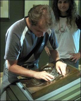 Görme Engelli bir genç dokunarak heykeli inceliyor