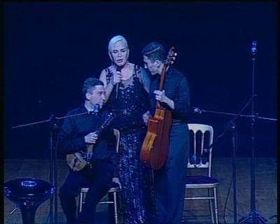 Selim Altınok,mandoliniyle sandalyede,elinde mikrofon Sezen Aksu ve gitarıyla Kerim Altınok ayakta sahnede